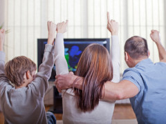 Family watching sports on TV and cheering.